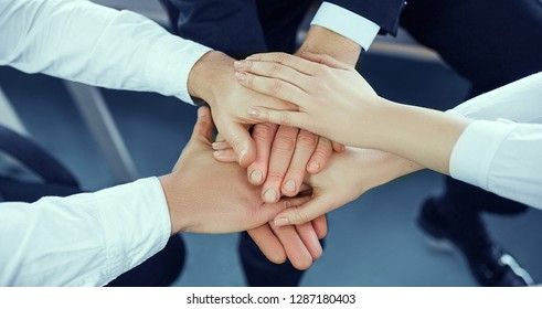 Male and female office workers, colleagues, teams folded in one pile. Top view on the hands united together