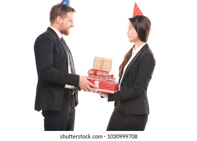 Male and female office workers wearing party hats and holding gift boxes