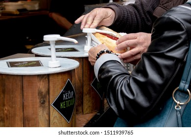 A Male and a Female at an outdoor hotdog stand in Prague The Czech Republic Europe, helping eachother putting mustard and ketchup on their hotdog. woman wearing black leather jacket.