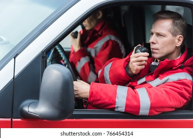 male and female paramedics talking by portable radios