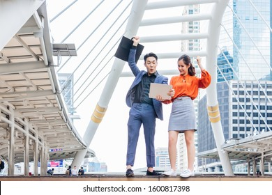 The male and female partner workers are very happy. They lifted their fists and had a bright face. With the backdrop of a tall building in the morning The concept of success is being raised in stock