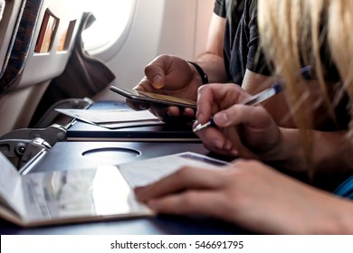 Male and female Passengers of Aircraft filling in Immigration Forms on tray Table holding Passports and Pens