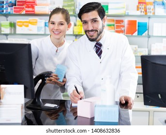 Male and female pharmacists are attentive stocktaking remedy with note near computer in pharmacy.
