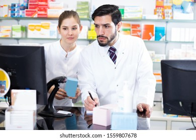 Male and female pharmacists are attentive stocktaking medicines with note near computer in pharmacy.