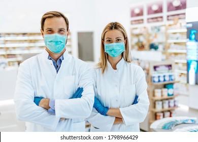 Männliche und weibliche Apotheker mit Schutzmaske auf ihren Gesichtern, die in der Apotheke arbeiten. Konzept der medizinischen Versorgung.