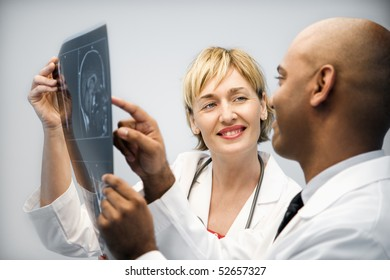 Male and female physicians holding and looking at patient xray film pointing and smiling.