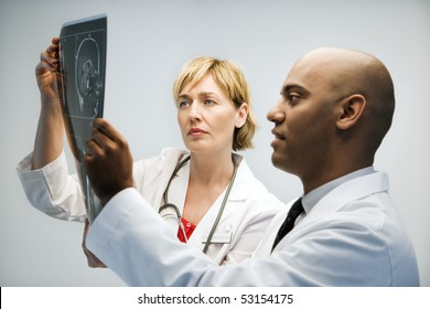 Male and female physicians holding and looking at patient xray film.