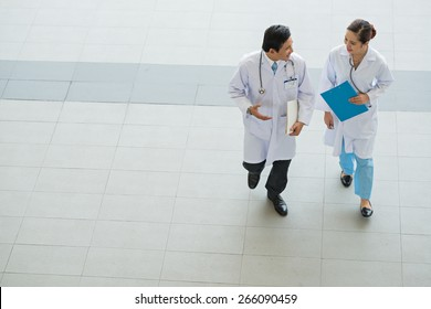 Male and female physicians talking while walking in the hospital, view from above