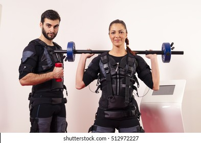 Male and female posing with weights next to ems machine