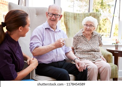 Male And Female Residents Sitting In Chairs And Talking In Lounge Of Retirement Home