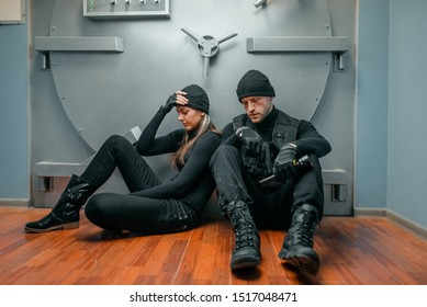 Male and female robbers trying to break vault lock