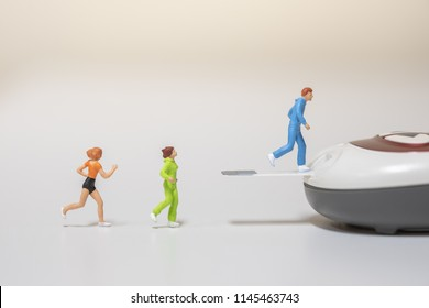 Male and female runner miniature figures running on blood sugar test strip and connect to Glucose meter. Sport, Fitness, Medicine, diabetes, glycemia, health care and people concept -