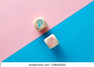 Male and female sex icons on wooden cubes on pink and blue background. Sex change, gender reassignment, transgender and sexual identity concept.