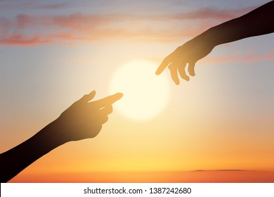 Male and female silhouette hands meeting one another on the beautiful sunset sky above the sea. The image depictures the concept of helping hand, relationship, love, faith, friendship and care.