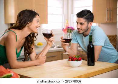 Male and female sipping red wine in the kitchen sharing a romantic gaze with chemistry