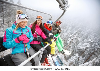 Male and female skiers in ski lift lifting on ski terrain