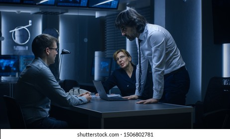 Male and Female Special Service Agents Interrogate Young Suspect in Cyber Crimes, Officer Looses Temper and Threatens Accused while Questioning. Dark Interrogation Room.