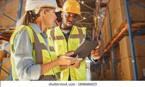 Male and Female Supervisors Holding Digital Tablet Talk about Inventory Check and Product Delivery in Retail Warehouse full of Shelves with Goods. Workers in Logistics Center. Portrait Shot