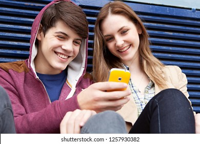 Male and female teenager friends sitting together in urban outdoors sharing smartphone, smiling networking holding device. Adolescent people enjoying using technology, recreation lifestyle.