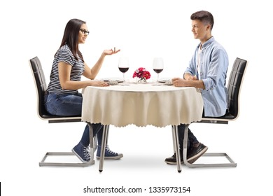 Male and female teenagers sitting at a restaurant table and talking isolated on white background