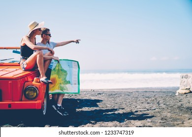 Male and female tourist making stop during journey on tropical island sitting on vintage rental car discussing next route, couple in love looking at map navigating during honeymoon on cabriolet