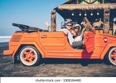Male and female tourists making car stop on ocean beach enjoying summer vacation together in roadtrip,hipster couple renting automobile for exploring Bali during honeymoon recreating on vacations