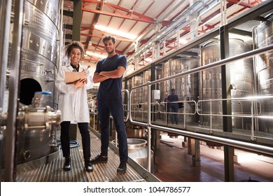 Male and female wine factory technicians smiling to camera