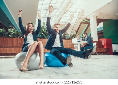 Male and female workers exercising stretching arms in office.