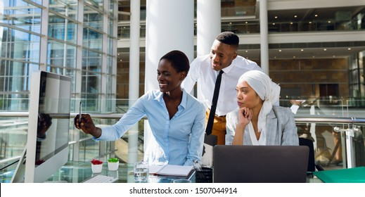 Male and females executives discussing over computer at desk in office. Modern corporate start up new business concept with entrepreneur working hard