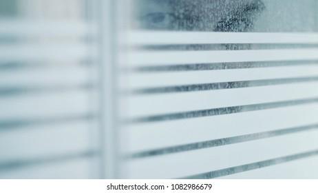 Male Figure Peering Through Window
