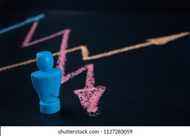 Male figurine with line graph drawin with chalk on blackboard and copy space