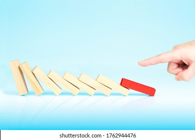 male finger pushing red block causing the domino effect