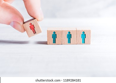 Male Fingers Adding A Block With A Different Colored Man Icon To 3 Blocks With Equal Colored Man Icons On A Table - Leadership Concept
