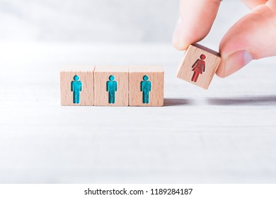 Male Fingers Adding A Block With A Different Colored Female Icon To 3 Blocks With Equal Colored Man Icons On A Table - Gender Equality Concept