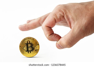 Male fingers push golden bitcoin away on a white background. Isolated man's hand throwing worthless cryptocoin away. Crash of cryptocurrency. Virtual money is depreciated. Useless bitcoins are kicked