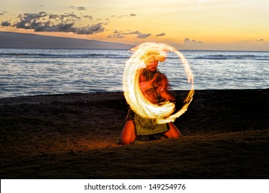 A male fire dancer kneels on a Hawaiian beach at dusk, spins a stick with fire to create a glowing circle of fire in the air.