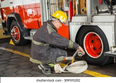 Male firefighter crouching while holding hose by truck at fire station