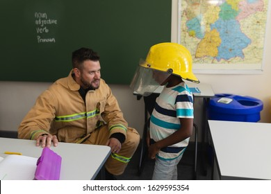 Male firefighter teaching schoolboy about fire safety in classroom of elementary school