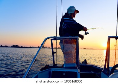 A male fisherman with a spinning rod in his hand catches fish from a boat at dawn.