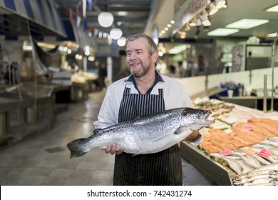 Male fishmonger wearing an apron holding large and whole salmon fish in front of display counter early in the morning on a market in England.