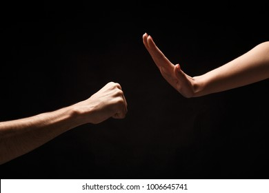 Male fist attacing and female hand in defense against black isolated backgorund. Stop violence against women concept, copy space