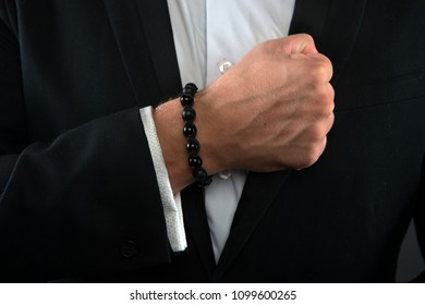 Male fist with bracelet on formal suit background. Bracelet or amulet on wrist. Amulet concept.