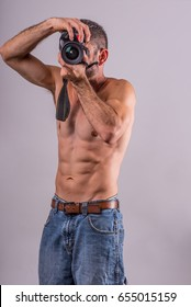 Male, fit person holding a DSLR Camera