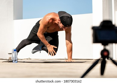Male fitness influencer recording ourdoor home exercise video clip with camera on rooftop