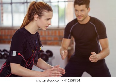 Male fitness instructor works with woman wearing ems equipment as she exercises in a studio