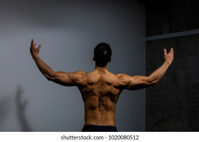 A male fitness model displays his back muscles. Medium shot.