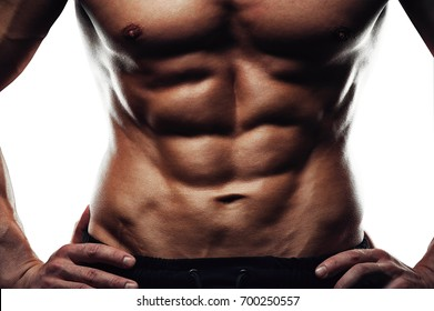 Male fitness model with naked torso showing sixpack abdominal and muscular body. Fitness and bodybuilding concept.