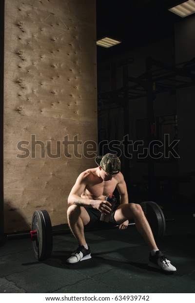 Male fitness model resting in the gym after workout with bottle of water