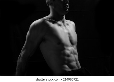 Male fitness model showing muscles in studio with a black background