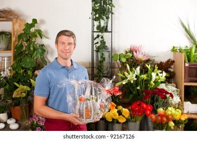 Male Florist in flower shop or nursery presenting his plants on display